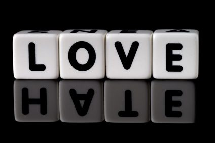 Love spelled in dice with the word hate reflected on black isolated background