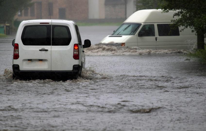 car rides in heavy rain on a flooded road