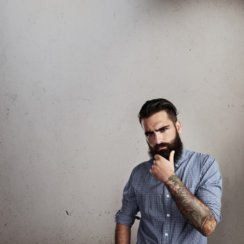 Portrait of thoughtful bearded man on concrete wall background