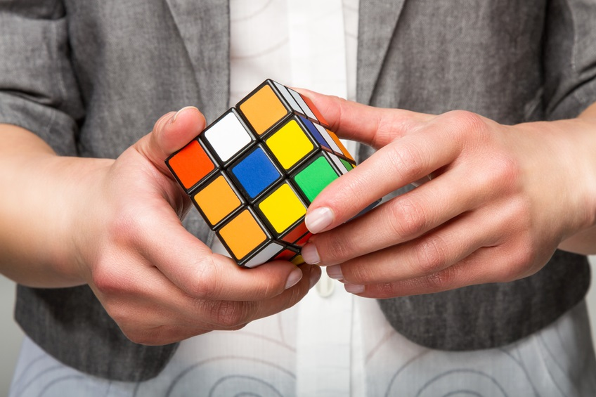 Hands holding or playing color cube game for concept solve solutionsolding color cube