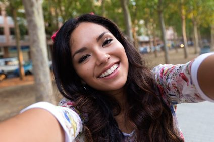 Outdoor portrait of pretty student girl taking a selfie.